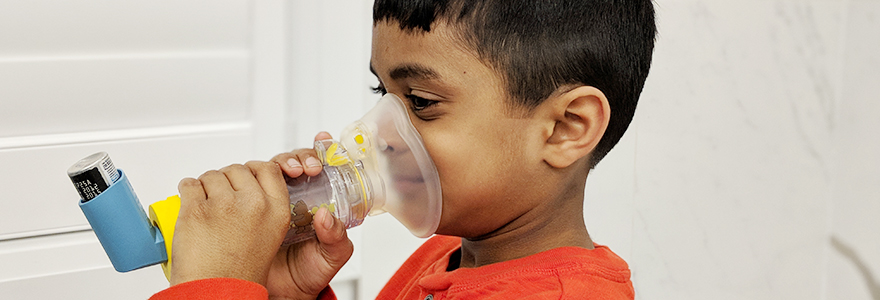 Young boy uses an inhaler and an aerochamber to take a medication to treat asthma
