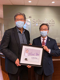 Dr. John Yoo presents Dr. Davy Cheng with a framed illustration